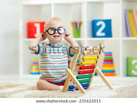 child toddler boy with eyeglasses playing abacus toy - stock photo