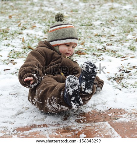Child toddler falling on icy slippery pavement or sidewalk in winter.  - stock photo