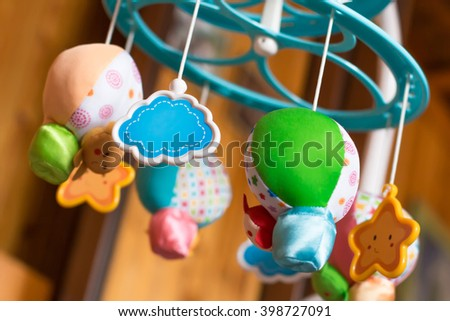 Child toy musical mobile air balloons with animals peeking out hanging on baby crib - stock photo