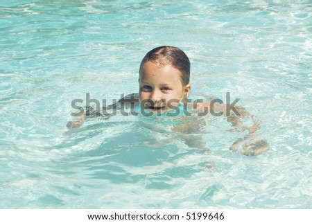 Child treading water in the pool - stock photo