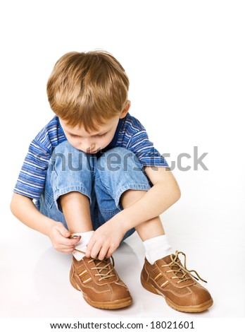 Child try to tie shoelaces - stock photo