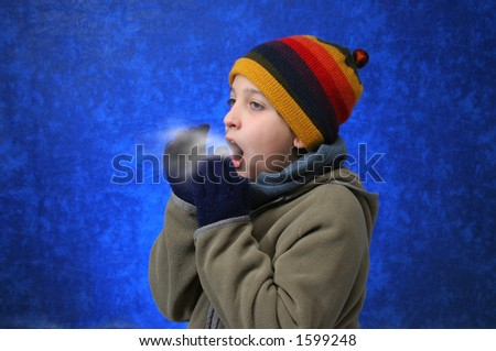 Child trying to warm his hands with his breath in winter outfit.