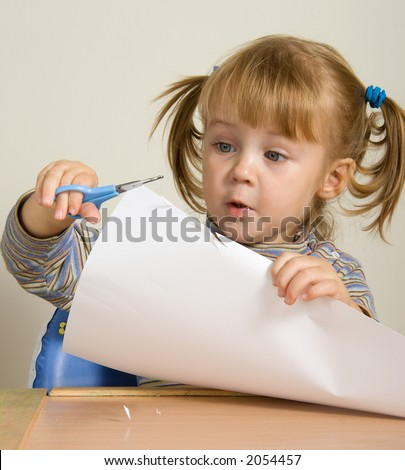 child two years cutting paper with scissors - stock photo