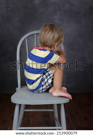 Child unhappy about school, on chair in classroom - stock photo