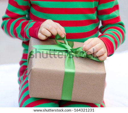 child untying and opening christmas present, shallow DOF, focus on bow - stock photo