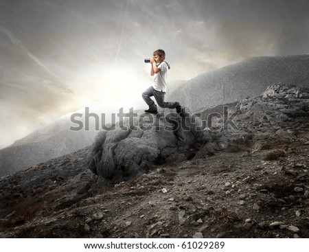 Child using a camera on a rock on the mountains