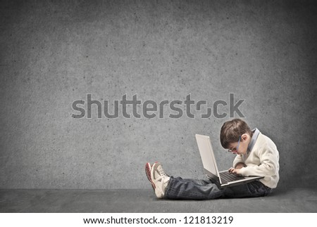 Child using a laptop computer with a dark white background
