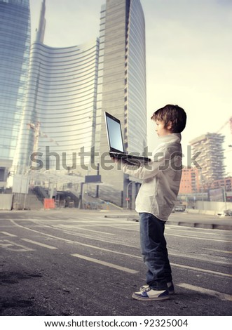 Child using a laptop on a city street - stock photo