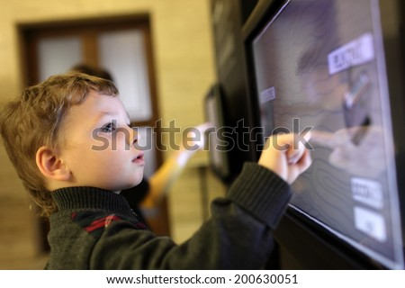 Child using interactive touch screen in a museum