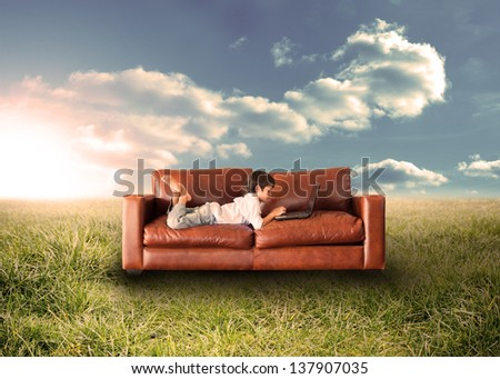 Child using laptop on couch in sunny field in the countryside - stock photo