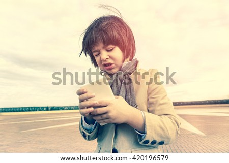 Child using mobile phone outdoor - Fashion kid making disappointed face playing smartphone on urban contest - Concept of children addiction using new technology - Vintage sadness editing - stock photo