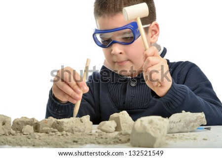 Child using tools at an archeology dig site - stock photo