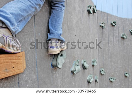 child venturing out on rock climbing wall - stock photo