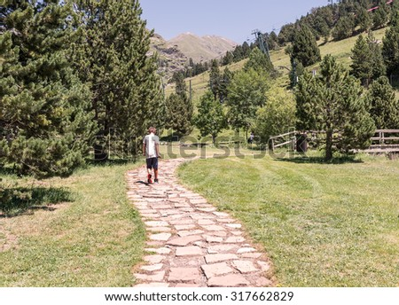 Child walking along a path between mountains - stock photo