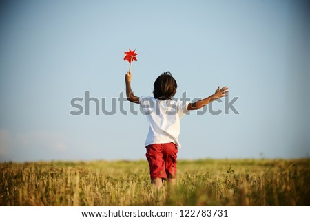 Child walking and running on field holding red spinning flower
