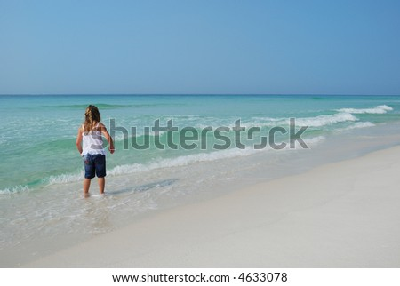 child walking on emerald coastline