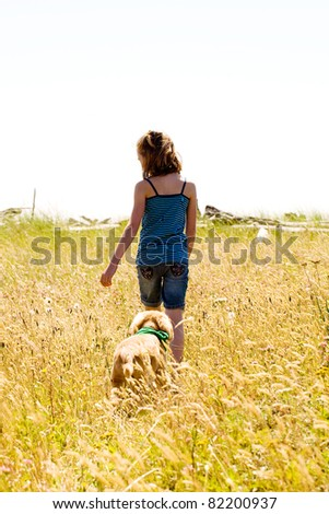 child walking with her dog on a trail