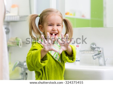 child washing hands and showing soapy palms - stock photo