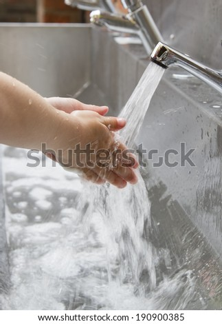 Child washing hands in a steel basin - stock photo