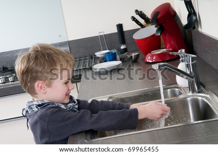 Child washing his hands before he is going cooking. - stock photo