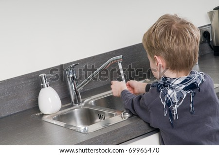 Child washing his hands before he is going cooking.