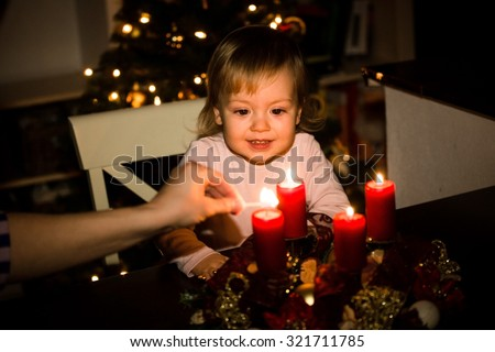 Child watching lighting of advent wreath with red candles, Christmas tree in background - stock photo