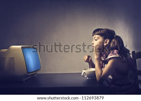 Child watching TV during the breakfast - stock photo