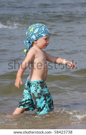 Child, water and fun. Baby boy have fun. Two years old baby boy on the beach. - stock photo