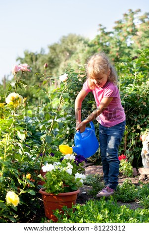 Child watered from watering the flowers in the garden