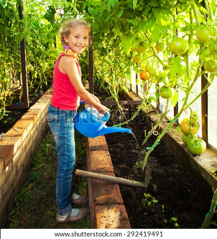 Child watering the garden. Girl helps to do the work in the greenhouse - stock photo
