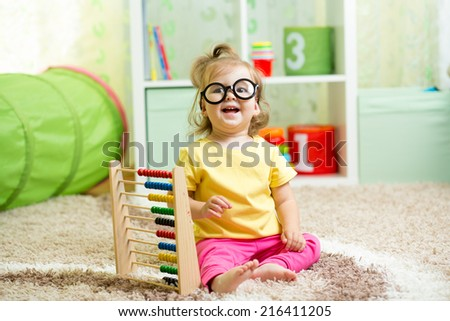 child weared glasses playing with abacus - stock photo