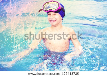 Child wearing a colorful swimming mask splashing water colors  in an open-air swimming pool - stock photo