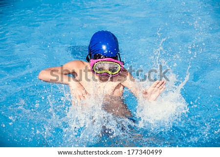 Child wearing a colorful swimming mask splashing water in a swimming pool  - stock photo