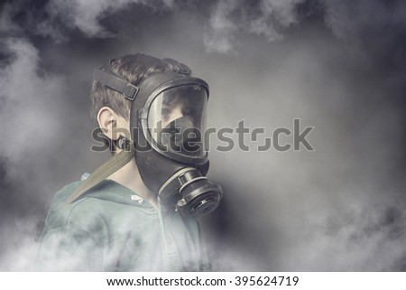 Child wearing a gas mask against air pollution - stock photo