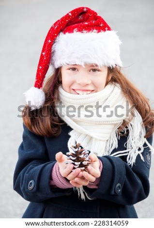 Child wearing Santa Claus hat holding pinecone - stock photo