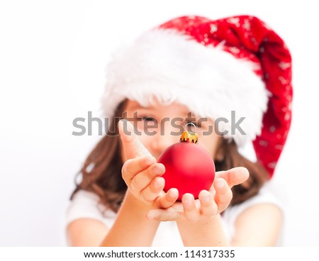 Child wearing santa claus  hat with a christmas ball - stock photo