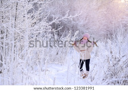Child winter outdoors. Lots of snow and frost. White tree branches. A girl stands in a frosty forest. - stock photo