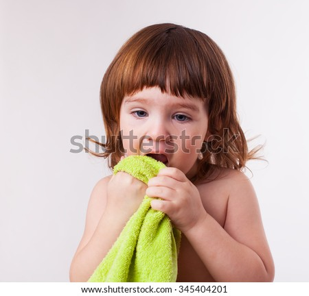 child wipes his face with towel