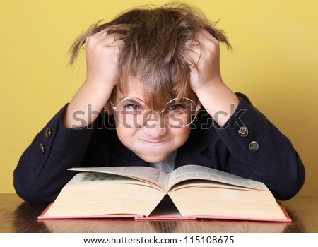 Child with a book on the desk - stock photo