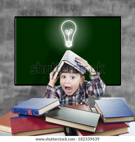 Child with a book over his head and a funny surprised expression - stock photo