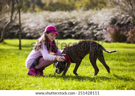 Child with a boxer dog at the city park - stock photo