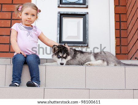 Child with a dog on the porch