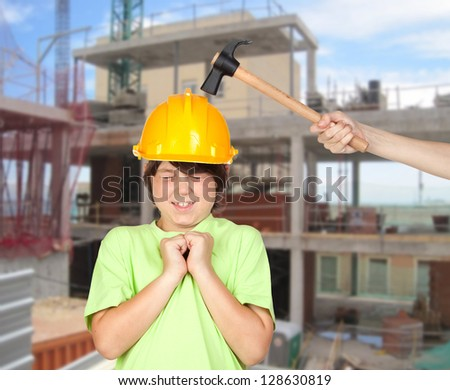 Child with a helmet on the work getting banged with a hammer