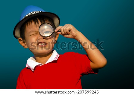 Child with a magnifying glass with a dark background. - stock photo