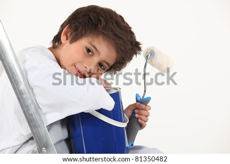 Child with a paint pot and roller - stock photo