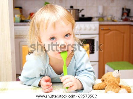 Child with a spoon photo in the kitchen - stock photo