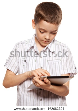 Child with a tablet pc. Boy playing on tablet isolated on white background - stock photo