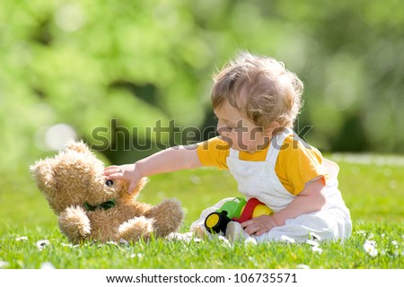 Child with a teddy bear on a summer meadow - stock photo
