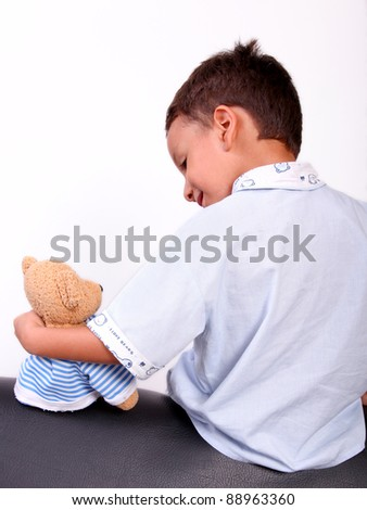 child with a teddy bear sitting with his back
