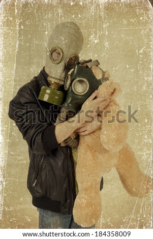 Child with a toy in a gas mask. Grunge effect. - stock photo